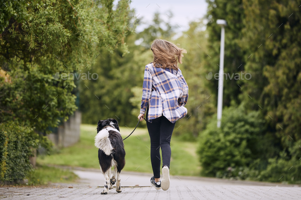 Rear view of teenage girl running with her dog down street - Stock Photo - Images