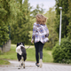 Rear view of teenage girl running with her dog down street - PhotoDune Item for Sale