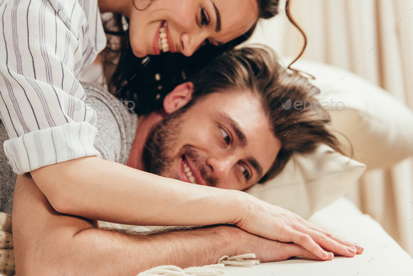 Close-up view of happy young couple hugging and holding hands at home - Stock Photo - Images