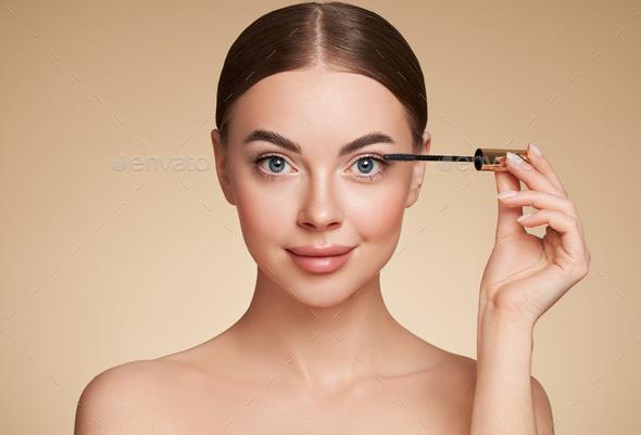 Beauty woman applying black mascara on eyelashes - Stock Photo - Images