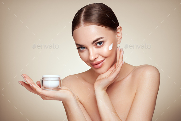 Beauty woman applying cream on her face - Stock Photo - Images