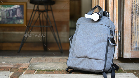 Tourist backpack and headphones on the road while waiting for the car, Travel concept. - Stock Photo - Images