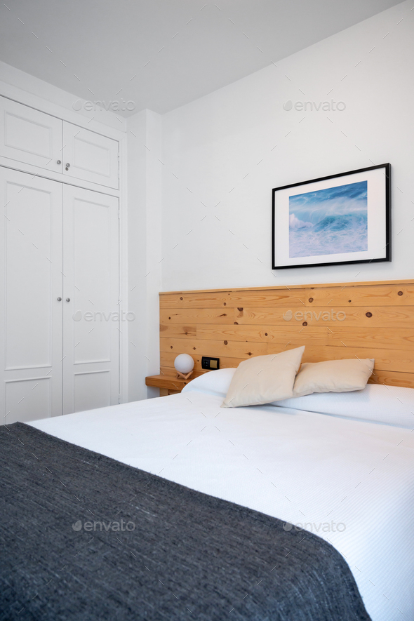 Bright white bedroom interior decorated with a photo of sea waves and a wooden headboard - Stock Photo - Images