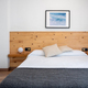 Bright white bedroom interior decorated with a photo of sea waves and a wooden headboard - PhotoDune Item for Sale