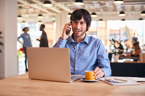 Businessman Sitting At Desk On Phone Call In Modern Open Plan Office - Stock Photo - Images