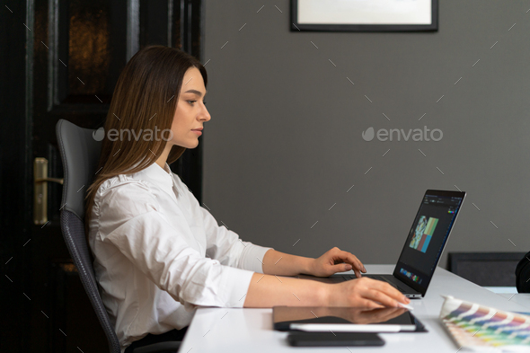 Portrait of young woman sitting at his desk in the office at laptop - Stock Photo - Images