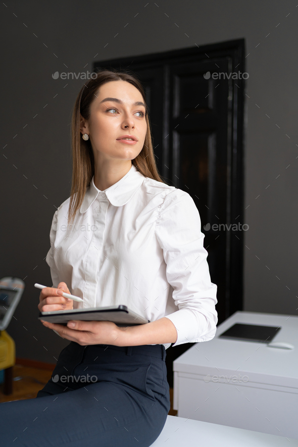 Young woman holding a digital tablet in the hands - Stock Photo - Images