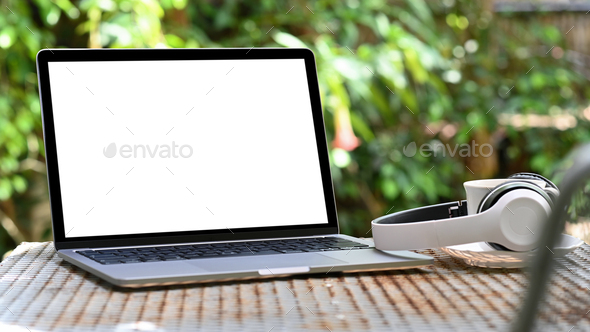 Mockup Laptop blank screen and headphone with coffee mug on iron table,Green tree background. - Stock Photo - Images