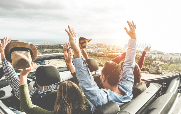 Happy friends with hands up having fun in convertible car on summer vacation - Stock Photo - Images