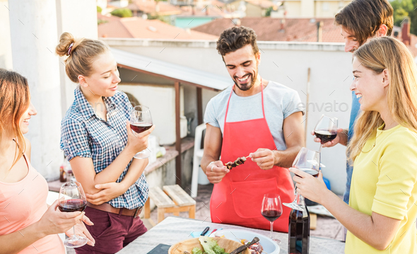 Happy friends having barbecue party on top of the roof - Stock Photo - Images