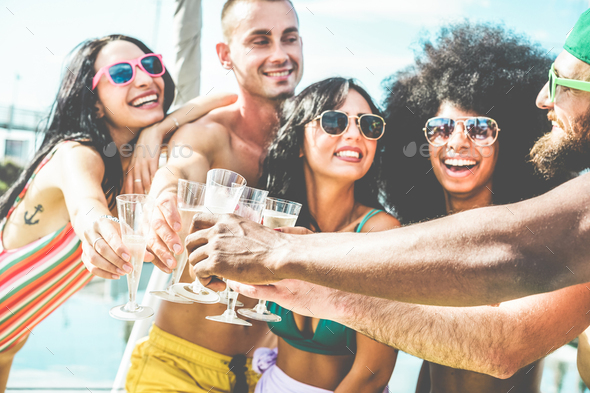 Happy friends cheering with champagne in summer boat party - Stock Photo - Images