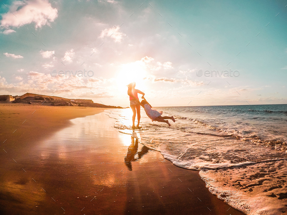 Mother and daughter having fun on tropical beach - Stock Photo - Images