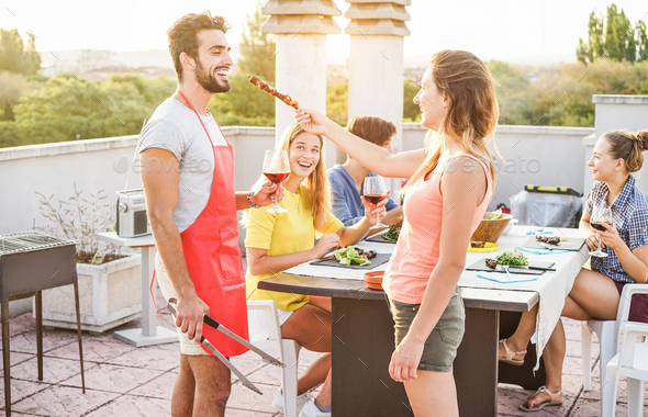 Happy friends eating and drinking red wine at barbecue party - Stock Photo - Images