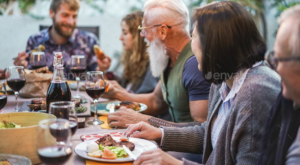 Happy family eating and drinking wine at barbecue dinner outdoor - Stock Photo - Images