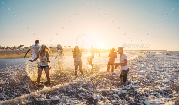 Happy friends having fun on the beach at sunset - Stock Photo - Images