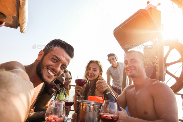 Group of happy friends taking selfie while drinking sangria in boat exclusive party - Stock Photo - Images