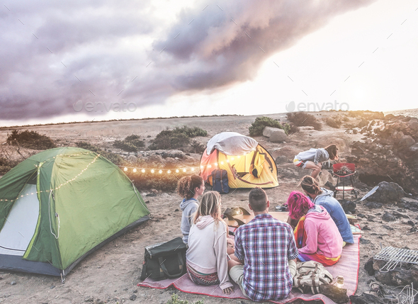 Happy friends doing barbecue picnic camping in the desert at sunset - Stock Photo - Images
