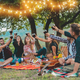 Happy friends having fun at picnic dinner with vintage lights outdoor next vineyard - PhotoDune Item for Sale