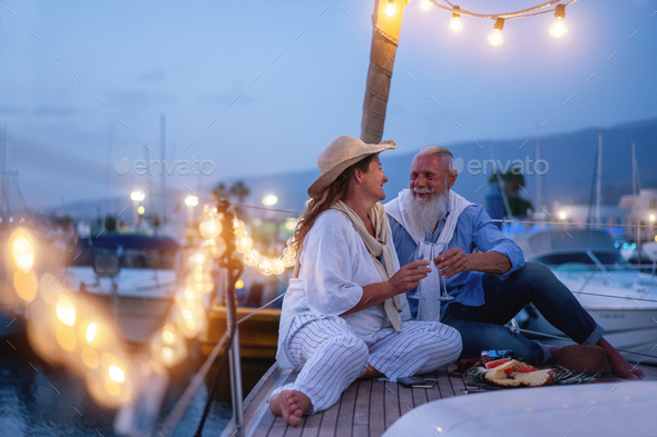 Senior couple cheering with champagne on a sailboat during wedding anniversary vacation - Stock Photo - Images