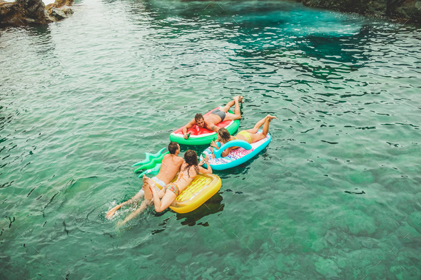 Happy friends floating with lilos mattress inside sea natural pool - Stock Photo - Images