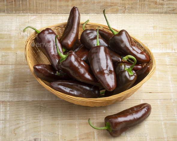 Basket with whole fresh chocolate mini pointed bell peppers close up - Stock Photo - Images
