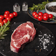 At the table, a raw Beef Entrecote with rosemary, salt and pepper on a round slate. - PhotoDune Item for Sale