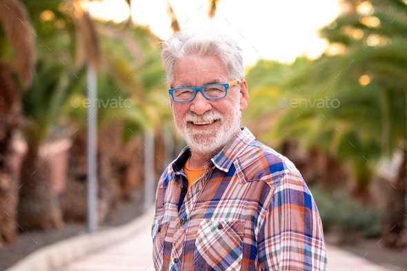 Portrait of attractive senior man white-hair and beard looking at camera. Standing outdoor - Stock Photo - Images