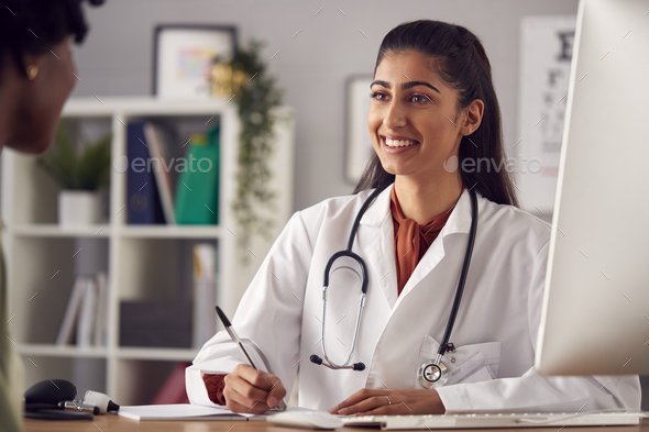 Female Doctor In White Coat Having Meeting With Woman Patient In Office - Stock Photo - Images
