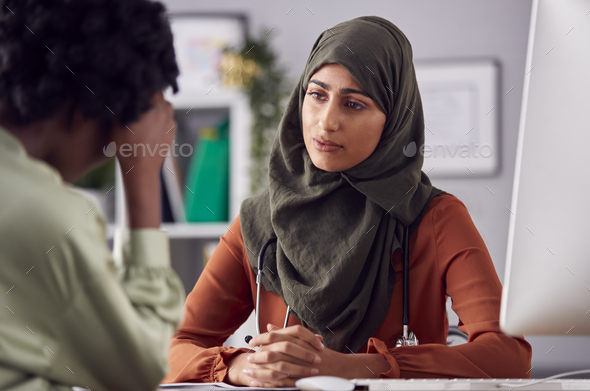 Female Doctor Or Consultant Wearing Headscarf Having Meeting With Unhappy Female Patient - Stock Photo - Images