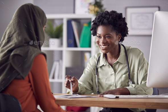 Female Doctor Or Consultant Having Meeting With Female Patient Wearing Headscarf To Discuss Scans - Stock Photo - Images