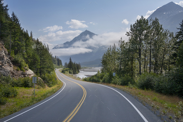 Camper travels along a curving highway in Alaska below mountains near Seward on a sunny afternoon - Stock Photo - Images