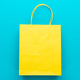 Top View Of Yellow Shopping Paper Bag On Blue Background - PhotoDune Item for Sale