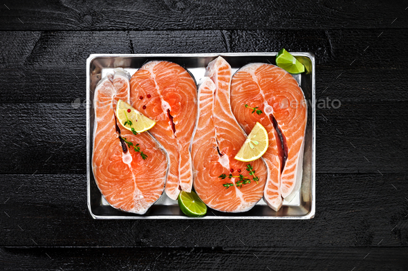 Salmon steaks on black wooden table top view - Stock Photo - Images