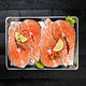 Salmon steaks on black wooden table top view - PhotoDune Item for Sale