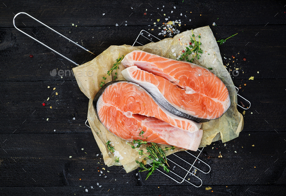Salmon steak on black wooden table top view - Stock Photo - Images