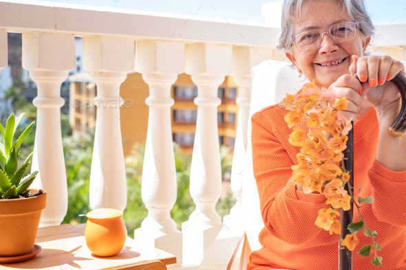 Front view of senior smiling woman suffering from osteoarthritis sitting with hands resting on cane - Stock Photo - Images
