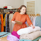 Positive female fashion designer checking rolls of fabric before starting work on new clothing - PhotoDune Item for Sale