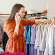 Young businesswoman owner of fashion atelier client on mobile phone and looking at dress collection - PhotoDune Item for Sale