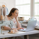Female fashion designer creating clothing design online while sitting at workplace with sewing - PhotoDune Item for Sale