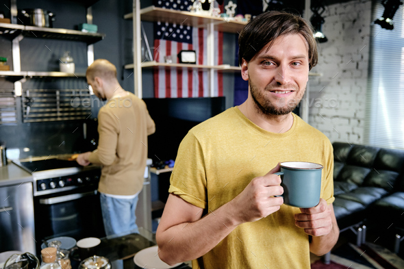 Smiling guy having drink in the kitchen - Stock Photo - Images