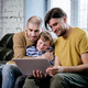 Affectionate men and cute little boy watching online video - PhotoDune Item for Sale