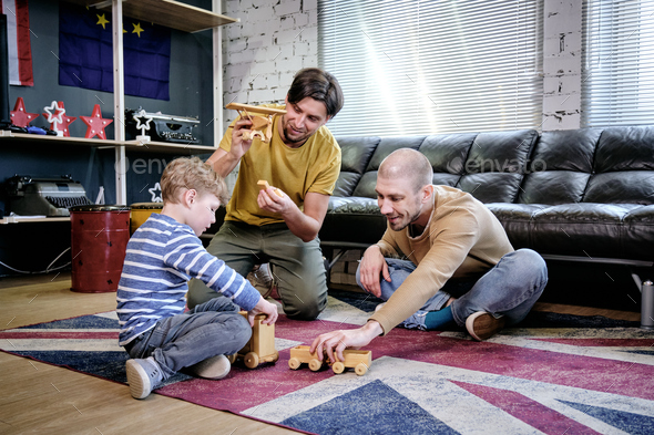Two young men and little boy playing on the floor - Stock Photo - Images