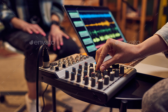 Hand of young female adjusting sound whil.e recording music - Stock Photo - Images