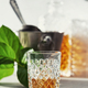 Glass of whiskey with ice cubes, ice bucket and carafe close up - PhotoDune Item for Sale