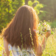 Rear view of beautiful young woman walking among wildflowers on sunny summer day. Concept of the joy - PhotoDune Item for Sale