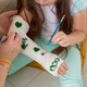 Mother and daughter drawing picture on bandage using paints close-up. Play therapy concept - PhotoDune Item for Sale