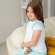 Child with a cast on a broken wrist or arm smiling and having fun on a couch. Positive attitude - PhotoDune Item for Sale