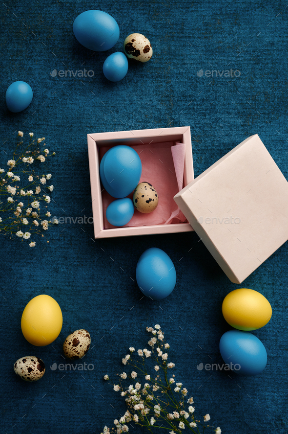 Easter eggs in gift box on blue cloth background - Stock Photo - Images