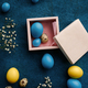 Easter eggs in gift box on blue cloth background - PhotoDune Item for Sale