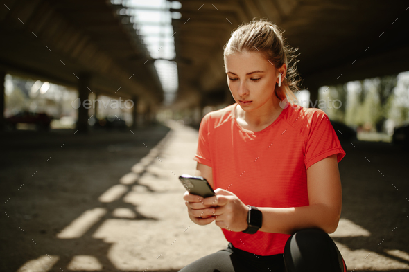 A blonde fitness girl with wireless earphones, plays music on her phone and starts running. - Stock Photo - Images